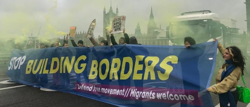 Protesters hold banner reading Stop Building Borders