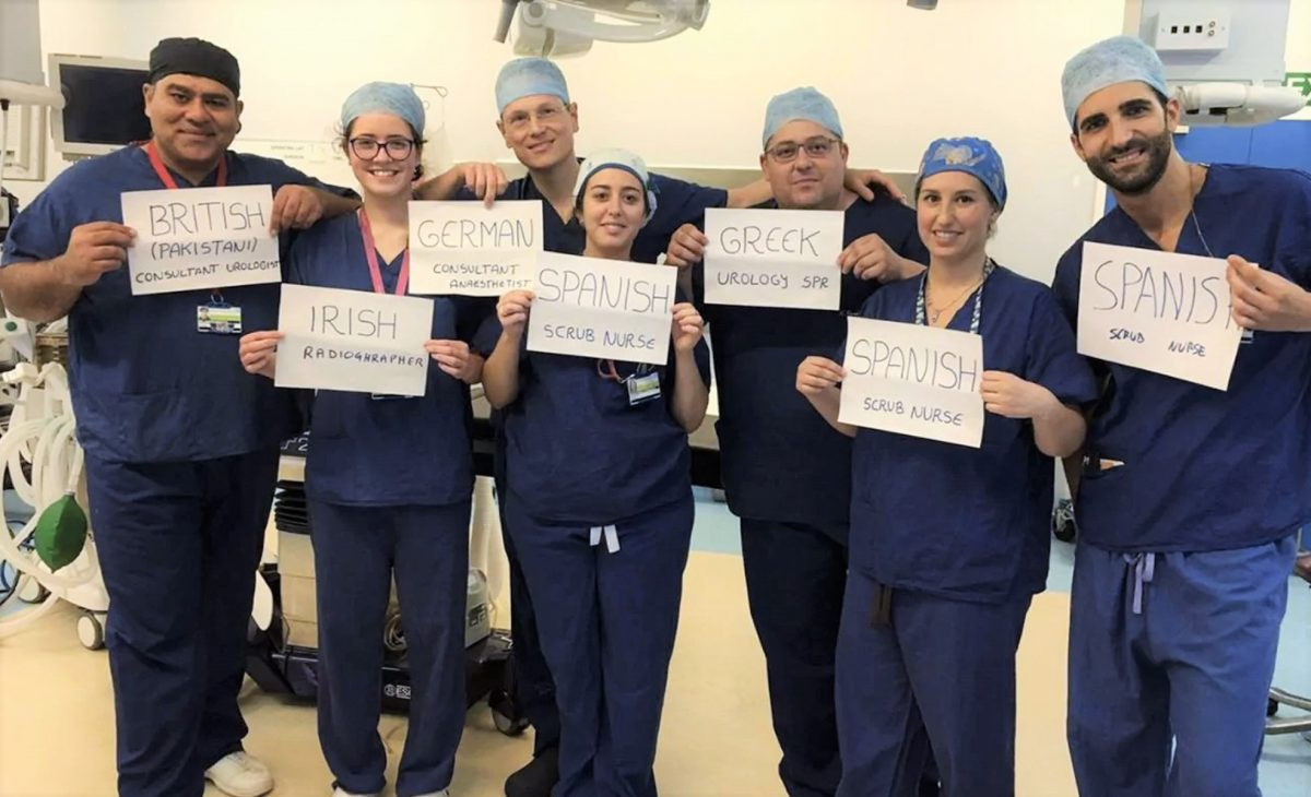 A team of NHS workers in scrubs hold signs declaring the different countries they come from.