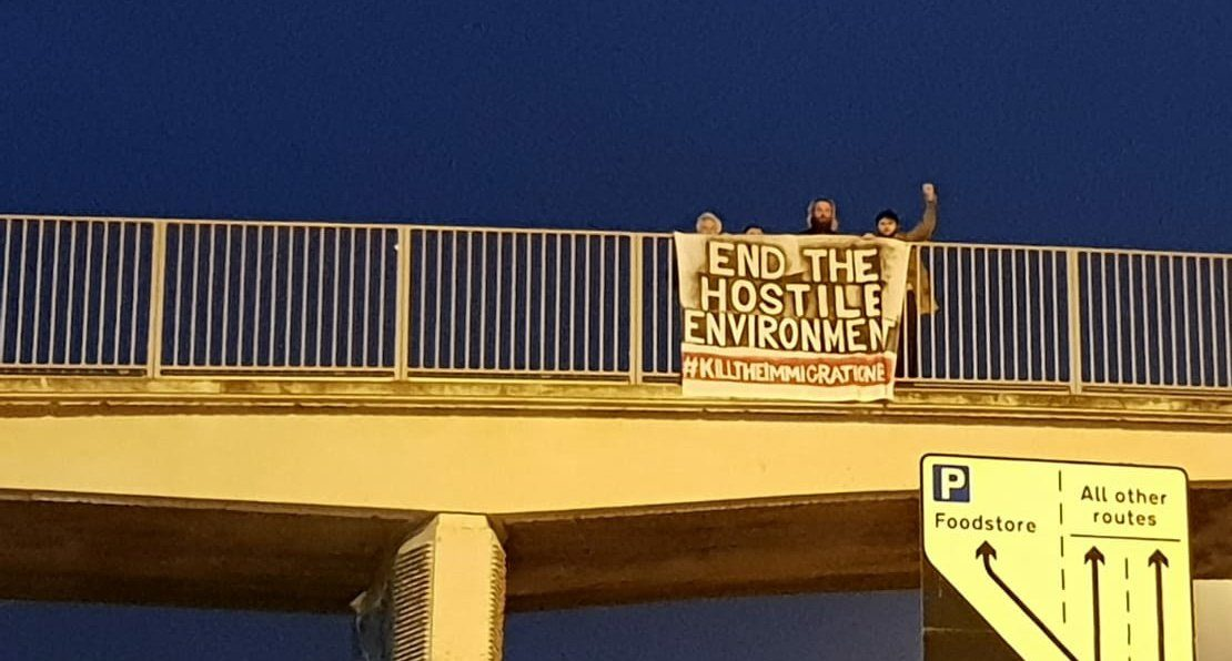 "Activists drop a banner reading ""End the hostile environment - kill the immigration bill"" from a motorway bridge"